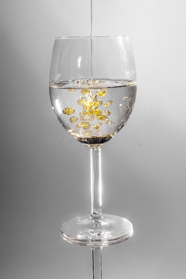 Clear Long Stem Wine Glass With Yellow Liquid stock photo