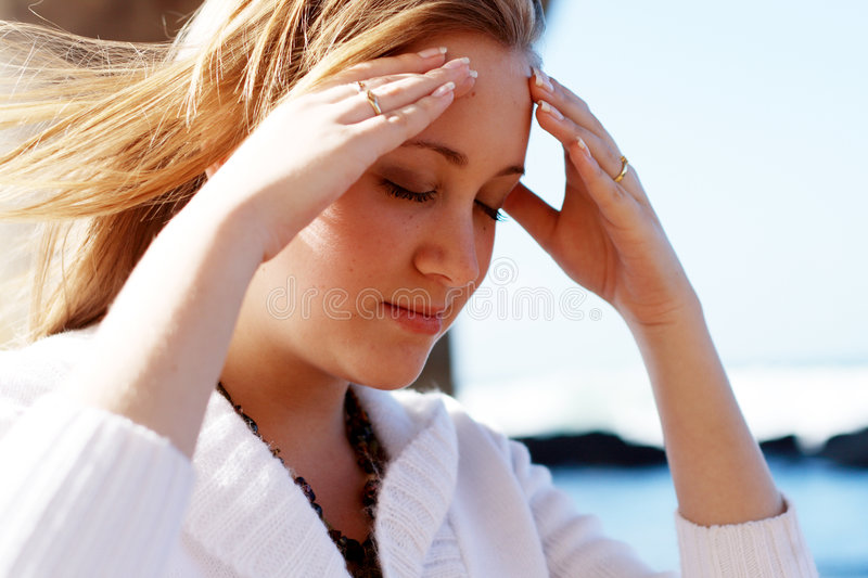 Clear mind. A young white woman with hands holding her head and wind blow through her hair. trying to clear her mind. photo taken on the beach royalty free stock photos