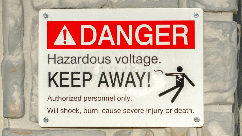 Clear Panorama Close up of Danger Hazardous Voltage Keep Away sign posted on a gray surface. The sign warns people that the dangerous voltage will cause shock royalty free stock photo