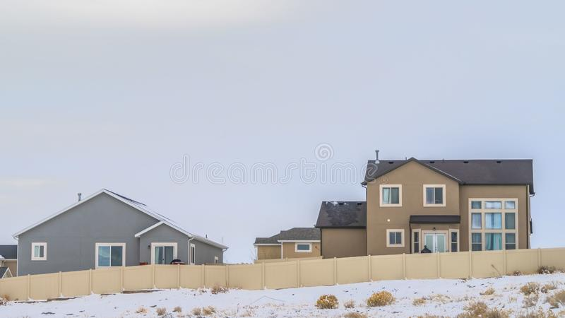 Clear Panorama Facade of houses with a boundless cloudy sky background in winter. A terrain coated with fresh powdery snow cna be seen in front of the wooden royalty free stock images