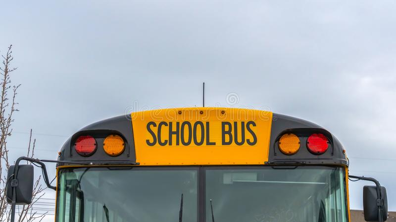 Clear Panorama Front view of a yellow school bus with homes and cloudy sky in the background. Several side mirros and signal lights can be seen at the front of stock images