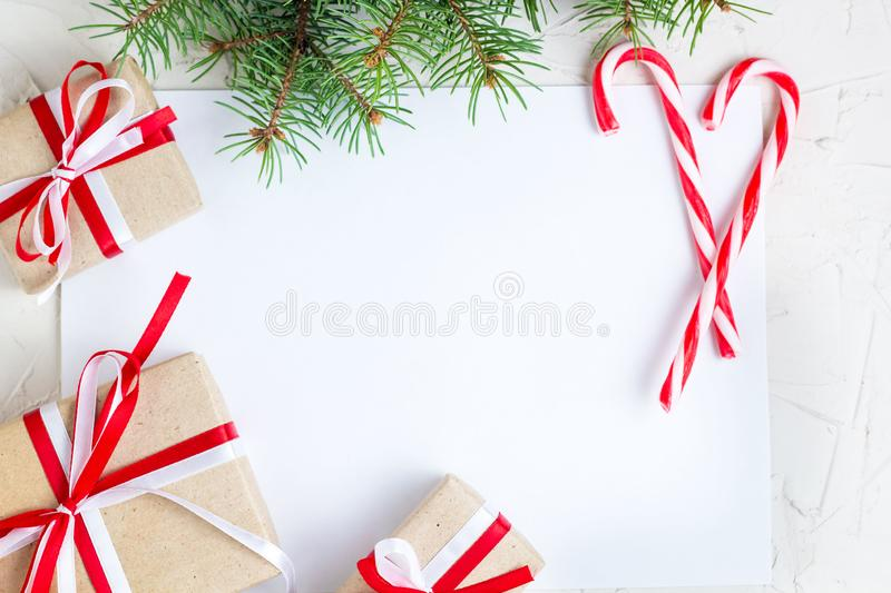 Clear paper laying with candy cane, Christmas tree branches and gifts royalty free stock image
