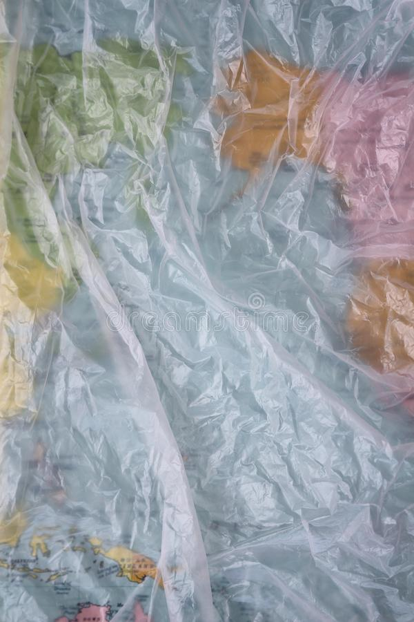 Clear plastic bag texture background. Earth map. Waste recycling concept. Crumpled polyethylene and cellophane. stock photo