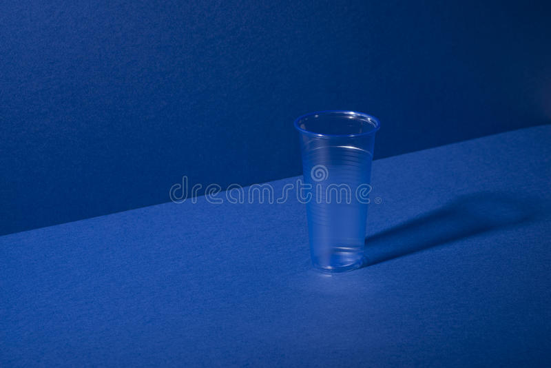 Clear Plastic Cup on Blue Background with Copy Space stock photos