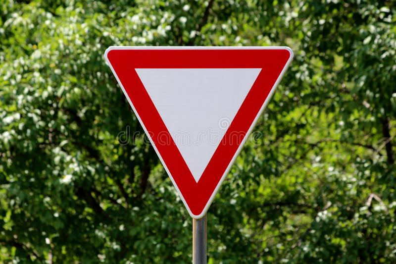 Clear red and white give way road sign mounted on strong metal pole with dense forest vegetation in back. Ground stock image