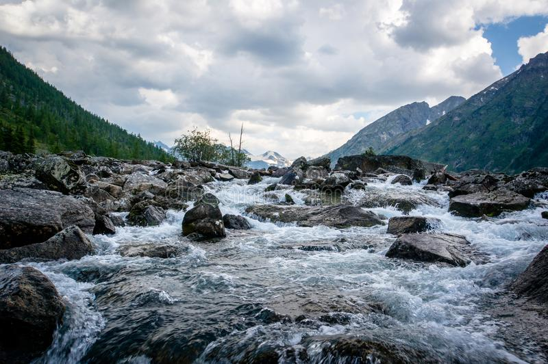 Clear river with rocks leads towards mountains. The river flows into the lake stock image