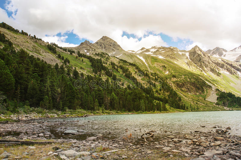 Clear river with rocks leads towards mountains royalty free stock images