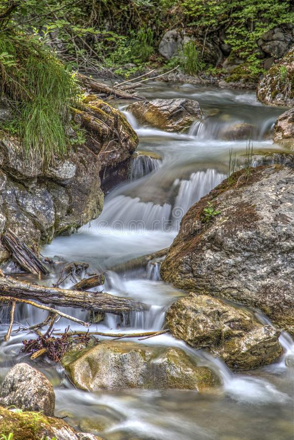 Clear Running Water in the Middle of Brown Stones stock image