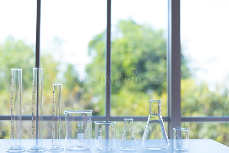 Clear scientific glassware, the different size of laboratory glassware, beakers or flasks on white table royalty free stock photos