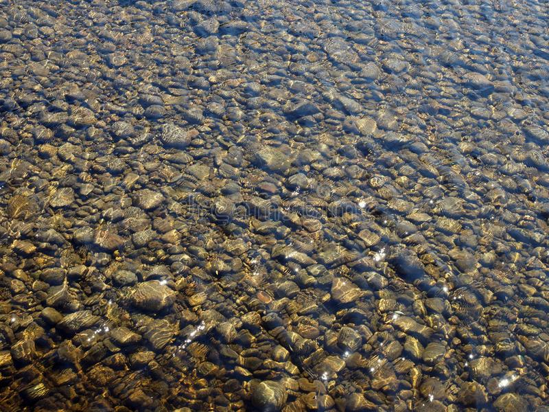Clear shallow river water flowing over pebbles stock photos