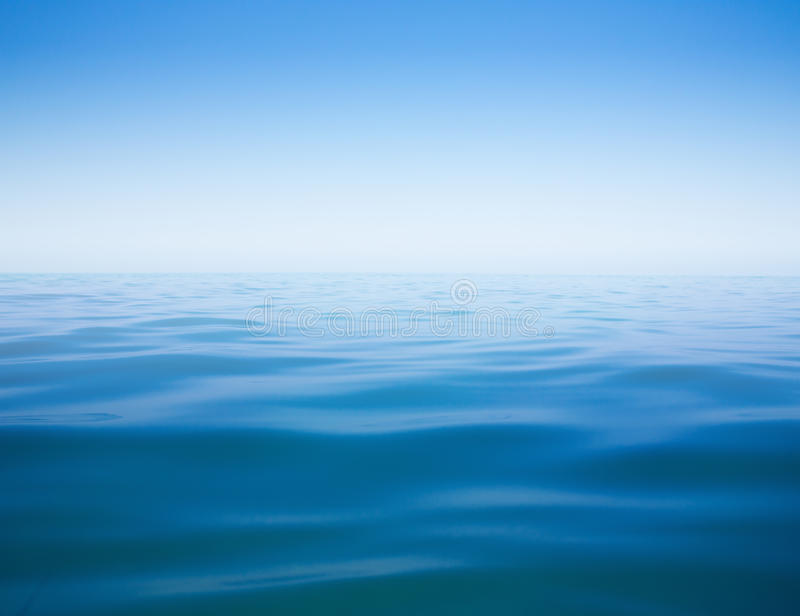 Clear sky and calm sea or ocean water surface stock photography