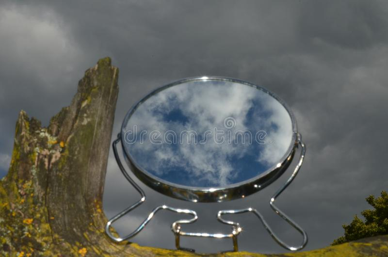 The true essence of reflection in the mirror. Clear sky in the glass of a mirror on the backdrop of a gloomy, rainy sky. Fighting opposites, good and evil, dark royalty free stock images