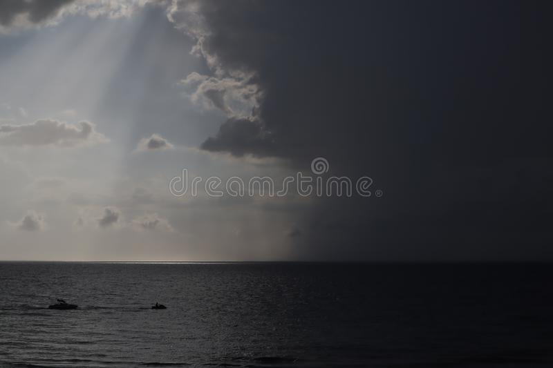 Clear sky and storm clouds on the sea. half the sky is clear, half are storm clouds. hurricane coming. storm coming on the ocean, royalty free stock image
