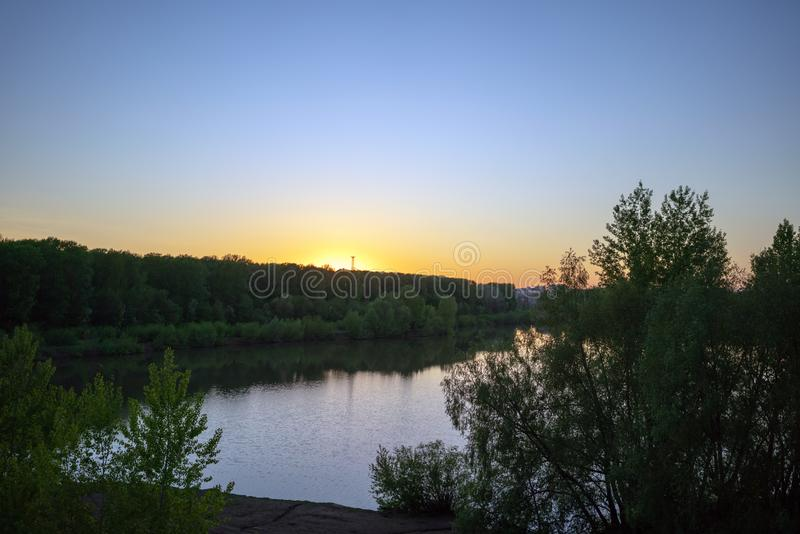 Clear sky sunrise, sunset over forest, river, sea. royalty free stock images