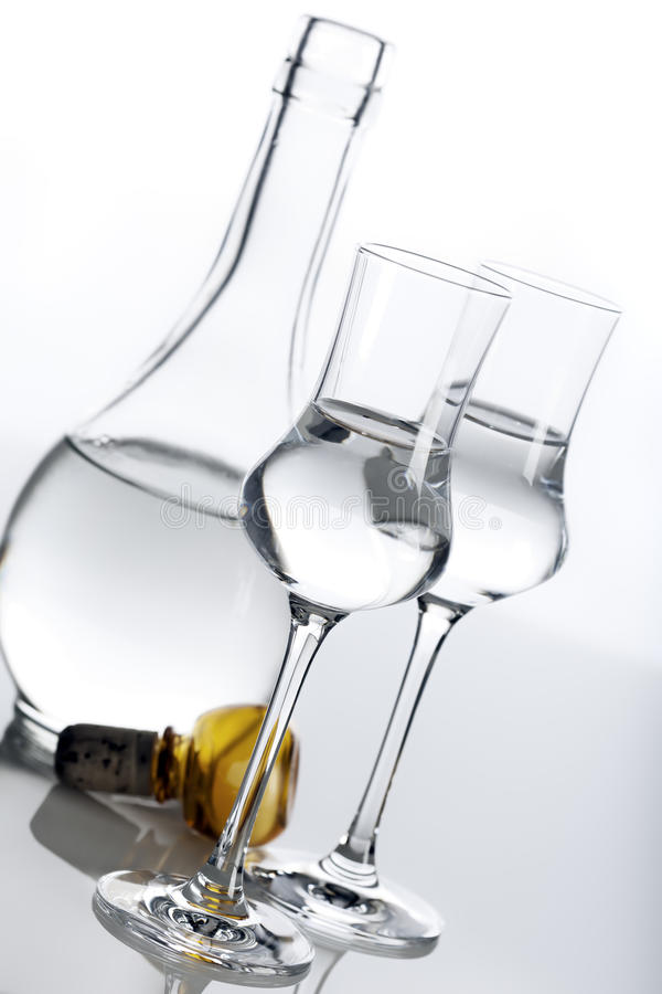 Clear spirit in carafe and glasses. Clear spirit in two glasses and carafe, tilted view royalty free stock photos
