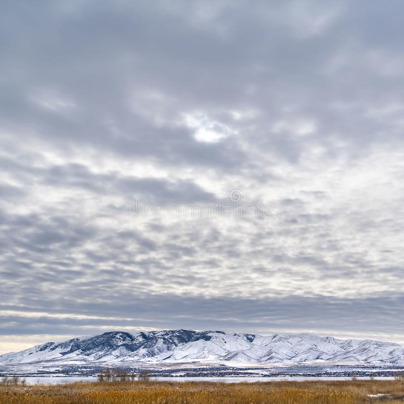 Clear Square Dramatic sky filled with cottony clouds over a scenic landscape in winter. A lake and snow capped mountain cna be seen beyond the vast grassy royalty free stock photography