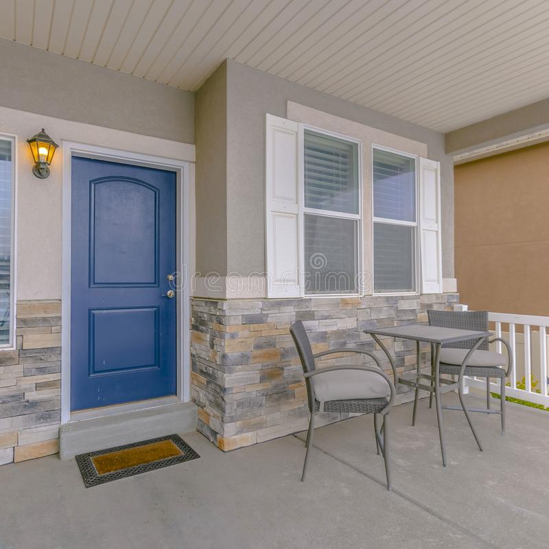 Clear Square Exterior of a home with blue wooden front door and reflective glass windows. Table and chairs can be seen on the fornt porch with white wooden royalty free stock images