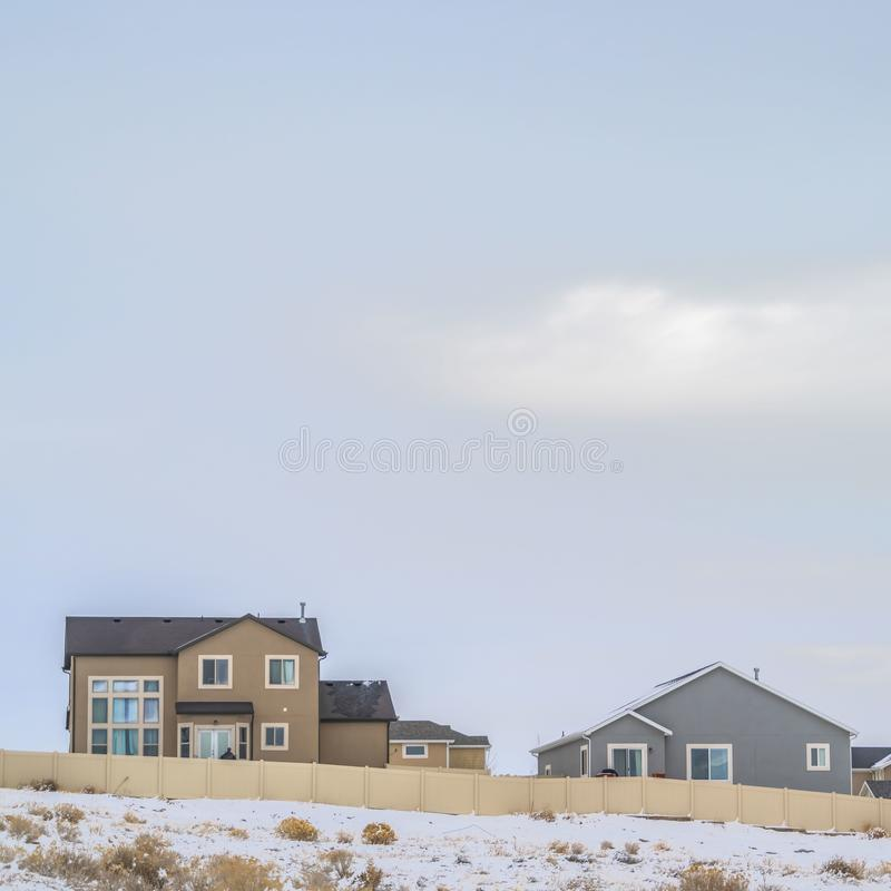 Clear Square Facade of houses with a boundless cloudy sky background in winter. A terrain coated with fresh powdery snow cna be seen in front of the wooden royalty free stock photography