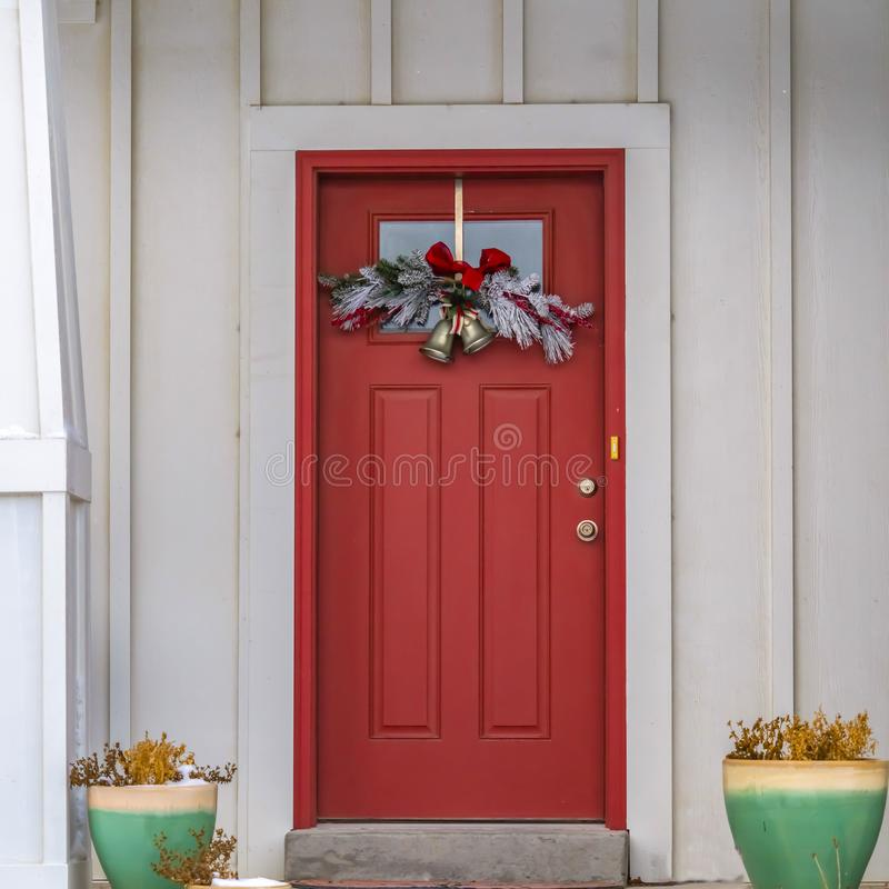 Clear Square Front door with glass panel and holiday decoration against a ribbed white wall. Plants on colorful pots adorn the outdoor stairs that leads to the royalty free stock photography
