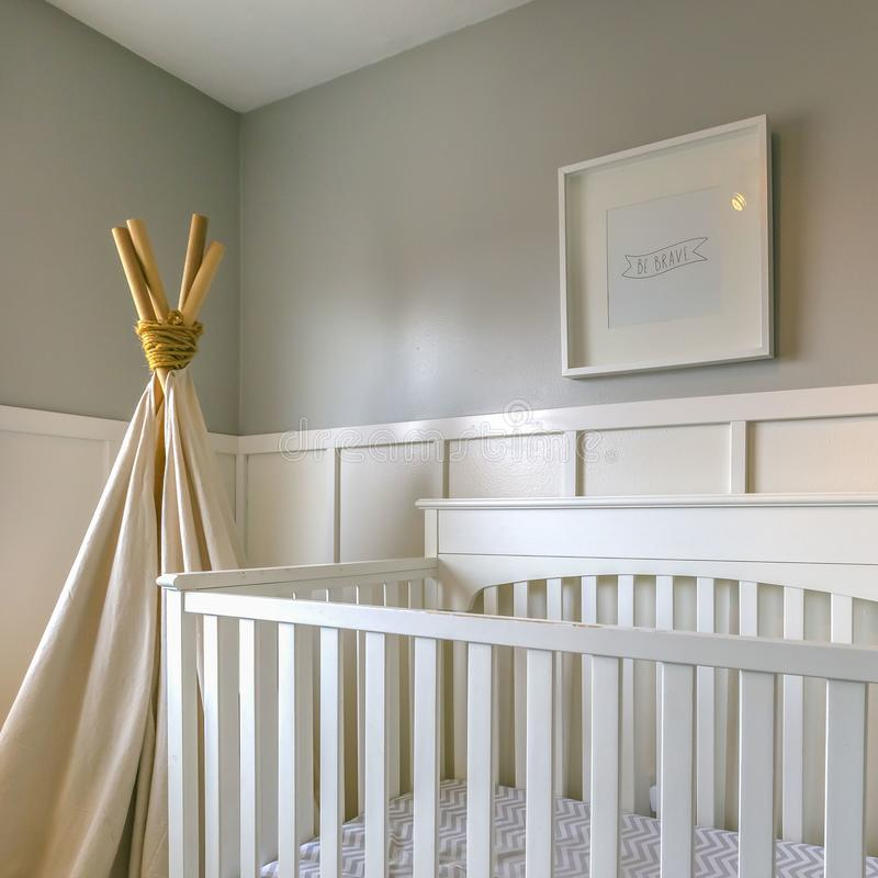 Clear Square Interior of a room for children with white wooden crib and play teepee. Sunlight streams inside the room with panellings on the wall through the royalty free stock photos