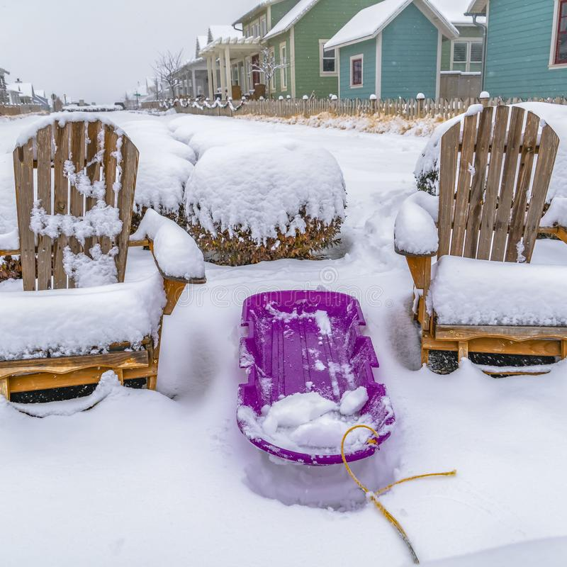 Clear Square Purple sled in the middle of wooden chairs on a frosted ground in winter royalty free stock photo