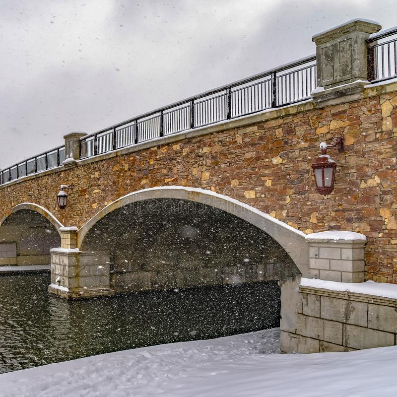 Clear Square Stone arched bridge with lamps over a lake during winter in Daybreak Utah. Snow falls down from the sky creating a blanket of snow on the stock images