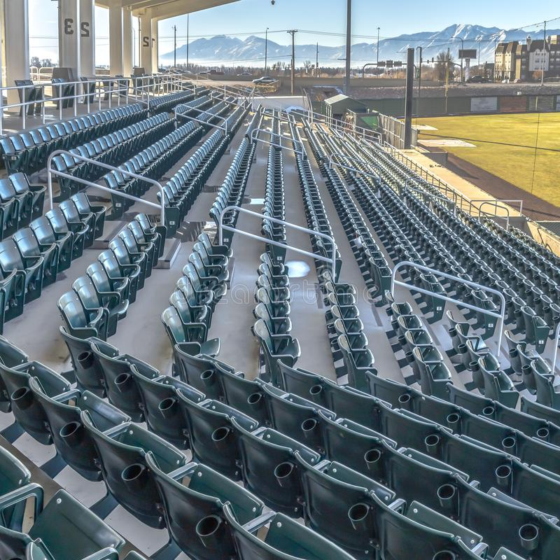 Clear Square Tiered seating and viewing rooms on a baseball field viewed on a sunny day. Building and snow caped mountain against blue sky can be seen in the royalty free stock photos