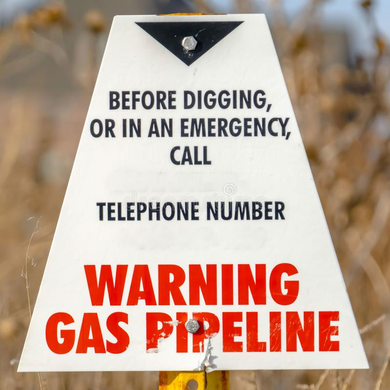 Clear Square Warning sign on an area with gas pipeline with trees and sky in the background royalty free stock images