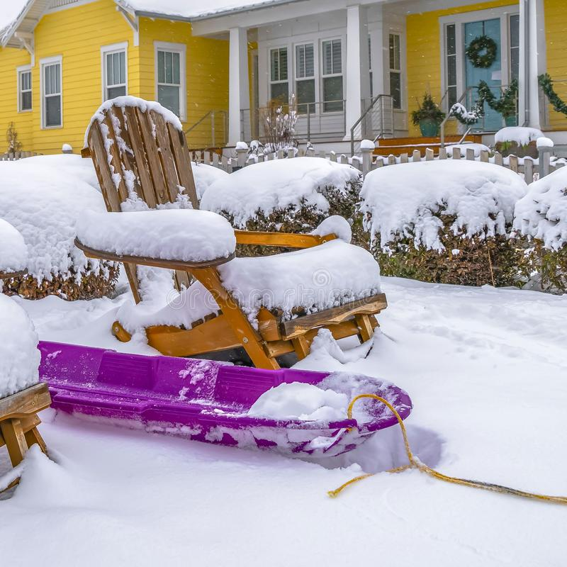 Clear Square Winter in Daybreak with view of a purple sled in the middle of wooden chairs stock photo