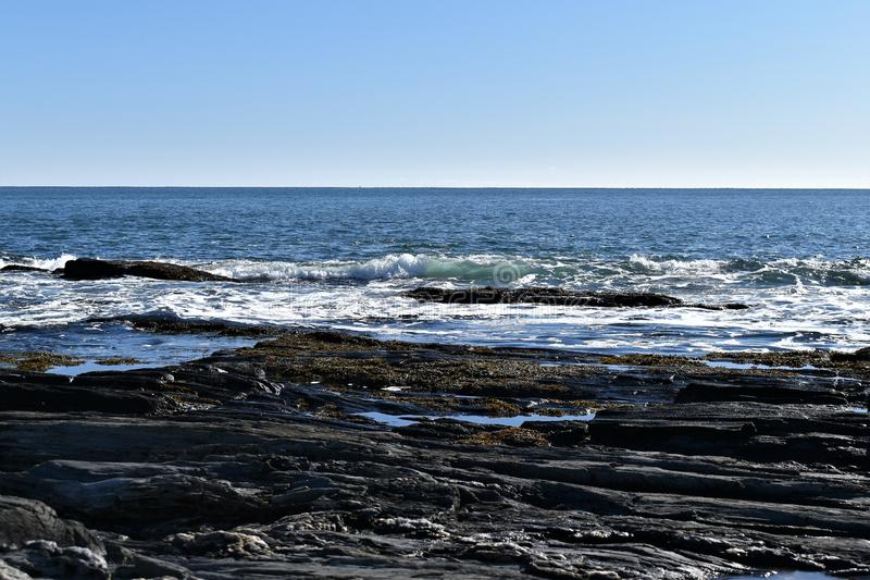 Cape Elizabeth`s rocky shoreline on Cape Elizabeth, Cumberland County, Maine, New England, US. A clear sunny cold winter day along the rocky shoreline at Dyer royalty free stock image