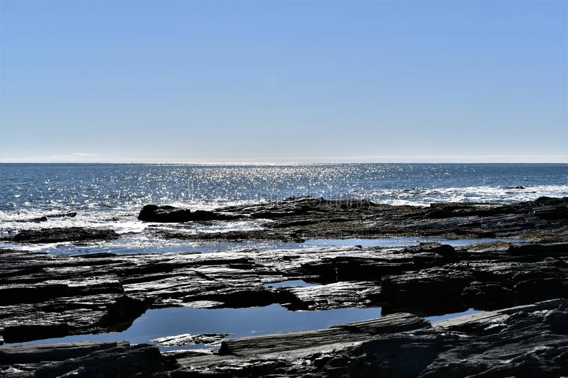 Cape Elizabeth`s rocky shoreline on Cape Elizabeth, Cumberland County, Maine, New England, US. A clear sunny cold winter day along the rocky shoreline at Dyer stock image