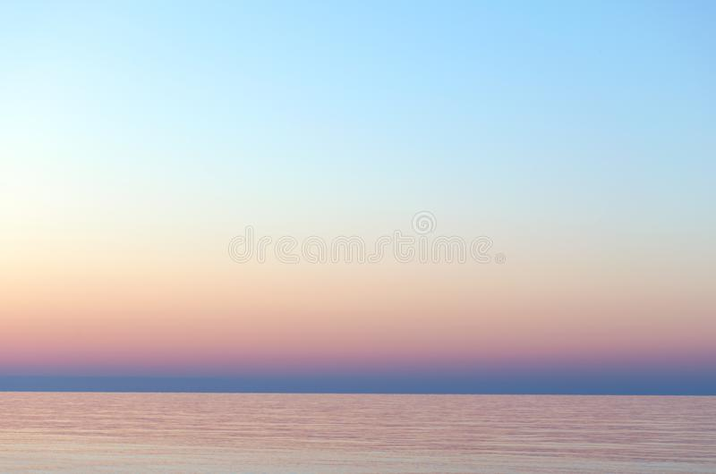 Clear sunset sky. Gradient background in pastel colors. Sunset over the sea. Beach dawn. Light nature exposure stock photos