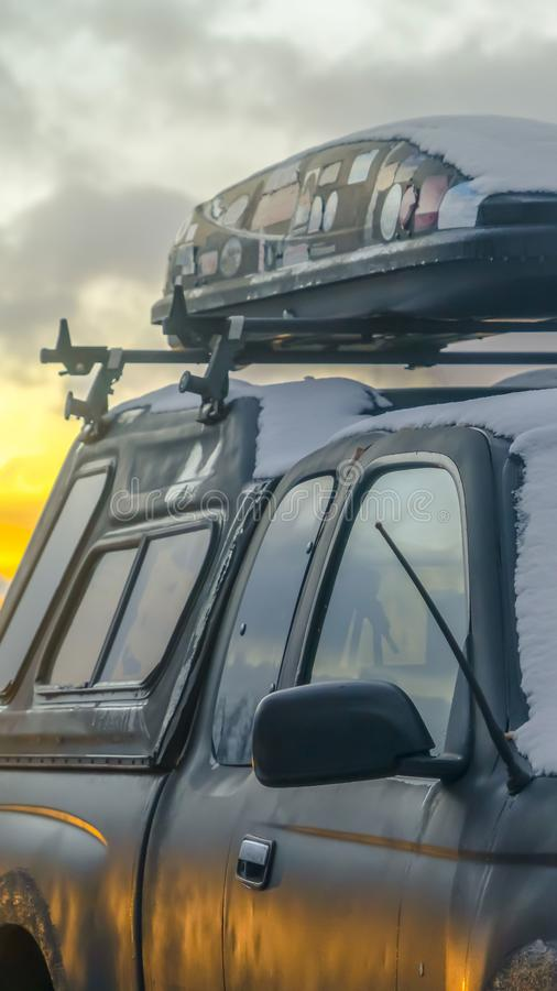 Clear Vertical Black vehicle with a roof rack and rooftop cargo carrier viewed in winter stock image