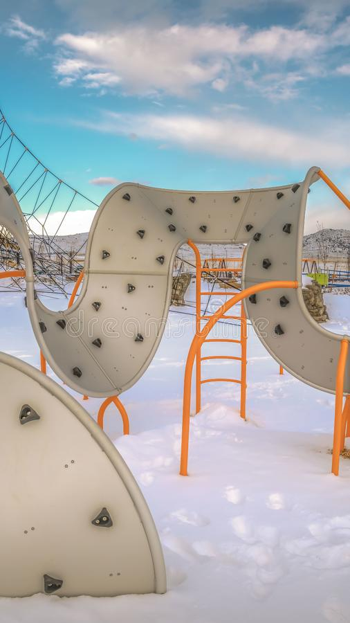 Clear Vertical Climbing frames on a playground with the ground covered with snow in winter royalty free stock images