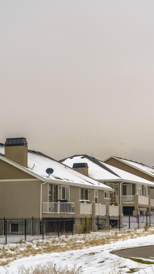 Clear Vertical Facade of homes viewed against snow capped mountain and white sky in winter royalty free stock photo