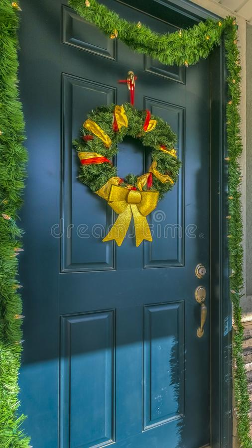 Clear Vertical Home with a sunlit porch and front door decorated with wreath and garland. The scenic mountain and vibrant blue sky are reflected on the sliding royalty free stock photo