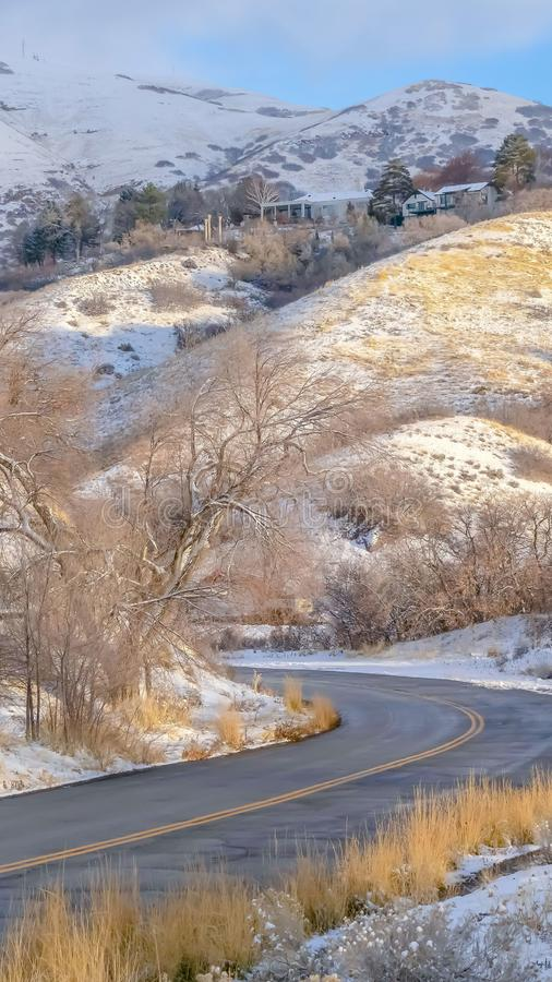 Clear Vertical Road and homes on sunlit snowy mountain in winter. Road curving through the snowy mountain in Salt Lake City on a sunny winter day. Homes and royalty free stock image
