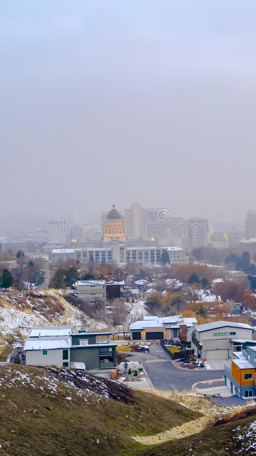 Clear Vertical Salt Lake City downtown against cloudy sky viewed from a snowy hill in winter. The historic Utah Stae Capital Building towers majestically over stock image