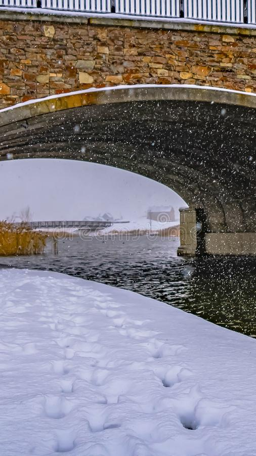 Clear Vertical Snowy trail along lake and passing under a bridge stock photography