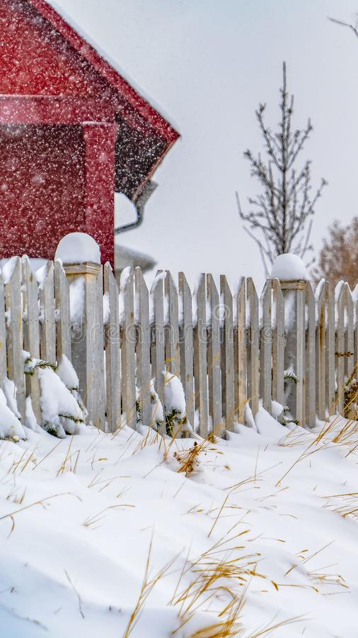 Clear Vertical Winter landscape with vibrant red home and snow topped picket fence in Daybreak royalty free stock photos