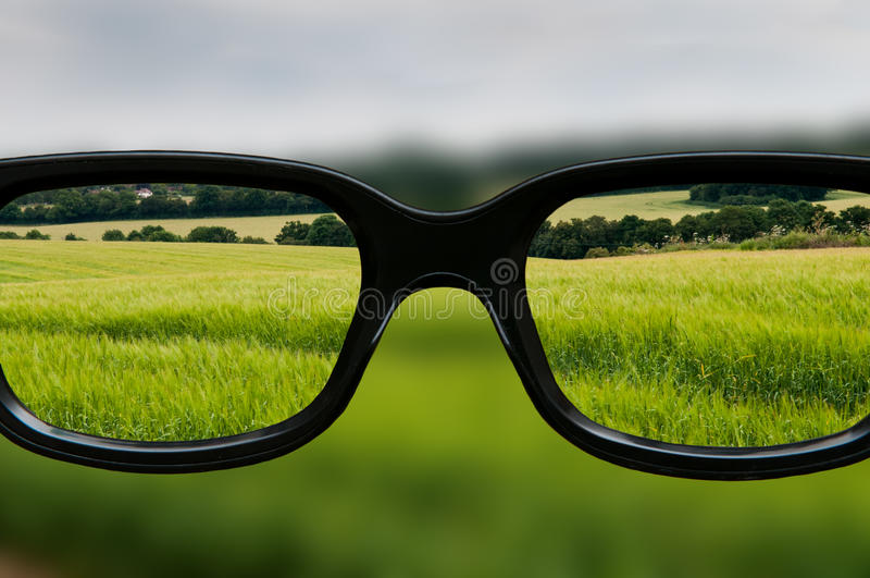 Clear vision through black framed eyeglasses. Looking over a landscape stock image