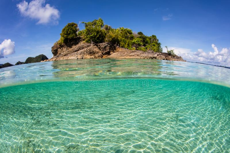 Tropical Island and Clear Water in Raja Ampat. Clear, warm water surrounds an island in Raja Ampat, Indonesia. This remote region is called the `heart of the royalty free stock photos