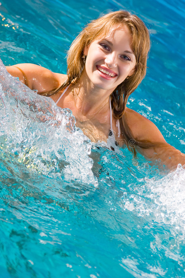 Clear water. Attractive young lady in clear water pool stock image