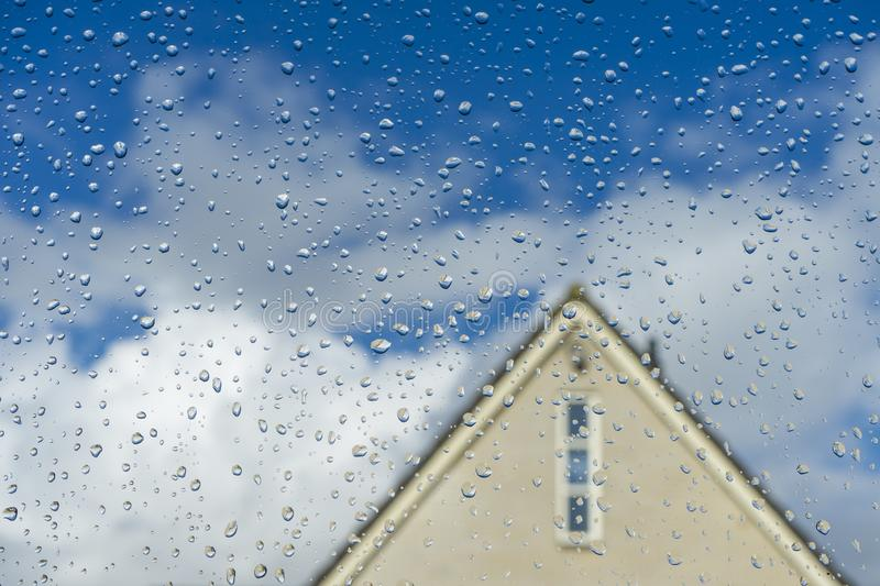Clear water drops on clean window glass with a house in the background. Super blue sky with white clouds water drupple on glass stock photo