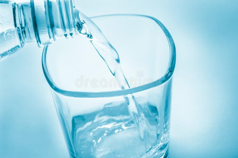 Clear water flows from the bottle into the glass. stock photo