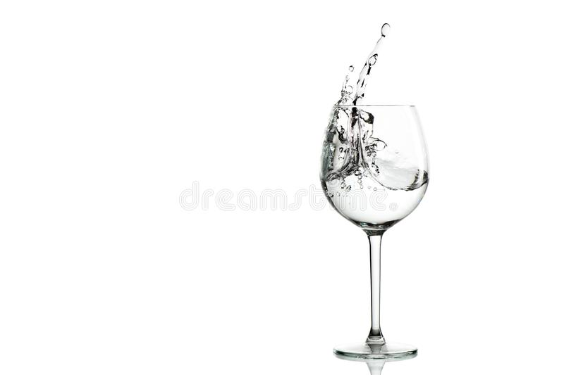 Clear water splashing in the wine glass. stock image