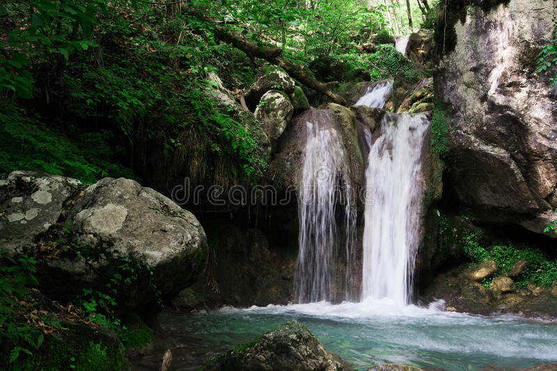 Clear waterfall in green forest, beautiful nature landscape stock image