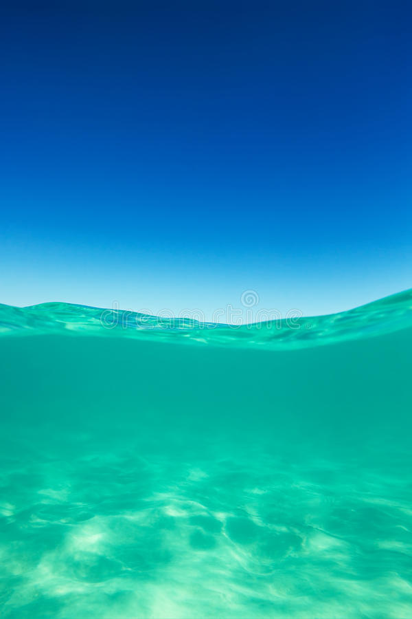 Clear waterline caribbean sea underwater and over with blue sky royalty free stock images