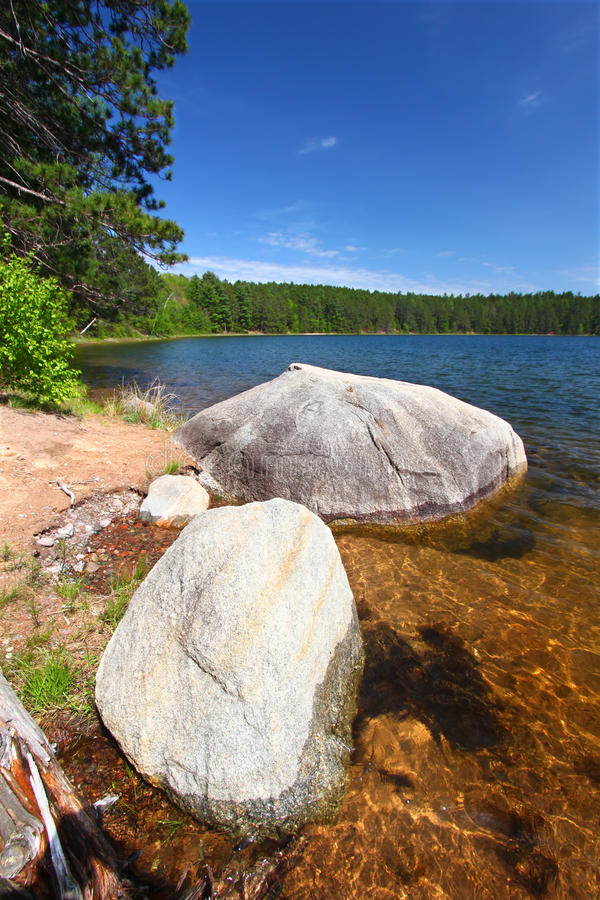 Clear Waters of Northwoods Wisconsin. Huge boulder along the shoreline of Buffalo Lake in the Northern Highland-American Legion State Forest of Wisconsin stock photos