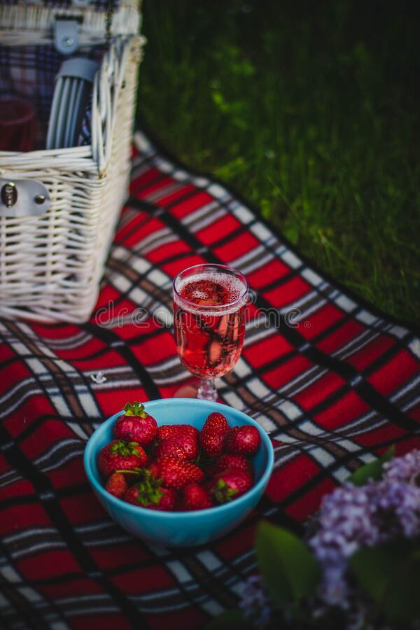 Clear Wine Glass With Wine Near Strawberry Fruit on Red White and Black Plaid Textile stock image